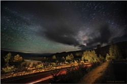 PHOTO BY DAVID WILSON - The Eel River Valley stretches into the distance beneath the living night sky in this view across the southbound lanes of U.S. Highway 101 from the Vista Point south of Stafford, Humboldt County. The three-minute exposure allowed the stars to form streaks along their paths across the sky. June 9, 2021.