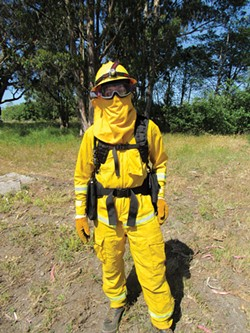 PHOTO BY LINDA STANSBERRY - CalFire firefighter Chris Lanza poses in the protective gear he'll wear on the fireline.