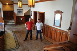 PHOTO BY GRANT SCOTT-GOFORTH - McKinlay and Neff stand in the Minor's lobby, stripped of carpeting and concessions equipment. Many of the lobby's fixtures, including the grandfather clock and opening night photo, remain.