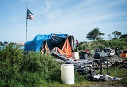PHOTO BY MARK MCKENNA - A tattered American flag flies over a soon-to-be razed camp in the PalCo Marsh on May 1.