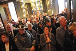 PHOTO BY MARK MCKENNA - Dozens of mourners fill the foyer during the funeral mass for slain Catholic pastor Eric Freed at Sacred Heart Church.