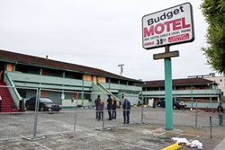 PHOTO BY THADEUS GREENSON - With the tenants having moved on, city officials watch as the last of the Budget Motel's windows and doors are boarded up.