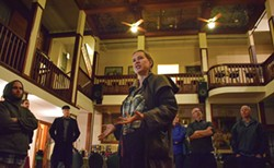 PHOTO BY JENNIFER FUMIKO CAHILL - Alex Service regales the tour group with tales of haunted rooms in the Eagle House Inn.