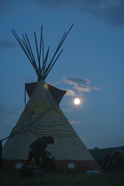 PHOTO BY ALLIE HOSTLER - Just before dinner, the moon rose over the Oceti Sakowin Camp. Singers and drummers could be heard throughout camp as others rushed to cover their camps with tarps to prepare for rain.