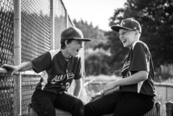 "PHOTO BY BRIAR PARKINSON - First Place Winner: John Harding, left, and Enzi Stuggard share a laugh with their team at the plate during a May 30 baseball game in Redway. ""I was taking action photos and then turned around and snapped this because friendships made, both with the kids playing and their parents, are such a big part of sports,"" explains photographer Briar Parkinson. ""These boys go to different schools but are friends through the sports community."""
