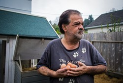 PHOTO BY JILLIAN BUTOLPH - Art Rush stands in front of his coop holding eggs from his chickens.