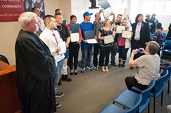 PHOTO BY MARK MCKENNA - Drug court graduates gather for a group photo March 23.
