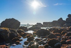 PHOTO BY MEGAN BENDER - The sun sets and glistens off tide pools at Luffenholtz Beach.