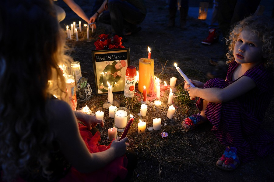 Valorie Mottern, 4, holds a candle near a photo of her cousin. - MARK MCKENNA