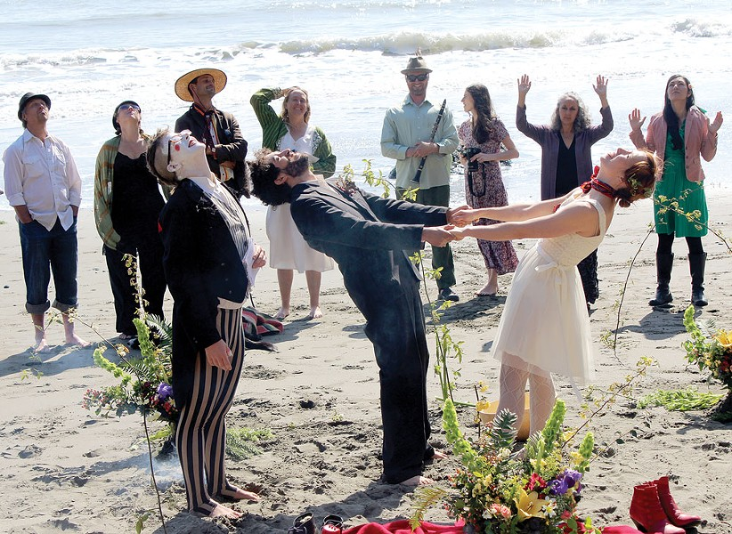 Willoughby and Isabelle Arevalo hold hands and look to the sky as family, friends and a clown named Elliot join them to celebrate their wedding vows on Saturday, March 22 at College Cove Beach. - PHOTOS BY BOB DORAN