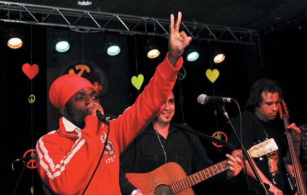 Winstrong, a reggae singer from Suriname, shows the peace sign while performing with the Berel Alexander Ensemble       at Increase       the Peace.