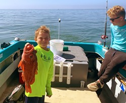 FISHY FISHY Eric Collier, 8, holds up the biggest catch of the day! A red rockfish that he caught himself out on the water near Port San Luis. - PHOTO COURTESY OF WIL COLLIER