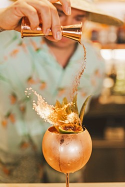 PICK YOUR POISON The Alchemists' Garden co-owner and bartender Tony Bennett sprinkles cinnamon into the flames of the Belladonna, butter-washed Krobar navel rum, pineapple and orange juice, falernum, and creme of coconut. - COURTESY PHOTOS BY SARAH KATHLEEN PHOTOGRAPHY