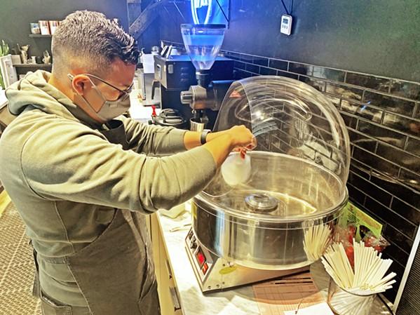 SUGAR RIDE Active Coffee Co. barista Pablo Arriola spins flavored sugar into a cloud pop ready to top a chai latte. - PHOTO BY CAMILLIA LANHAM
