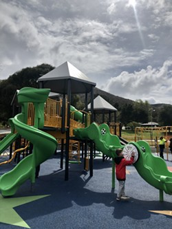 PLACE TO PLAY A young Lompoc resident tinkers with Beattie Park's new inclusive playground shortly after its unveiling. - PHOTO BY MALEA MARTIN