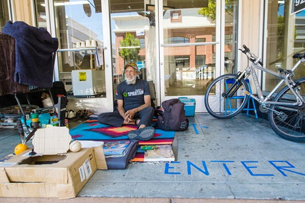 DOWNTOWN HOME Jeb, homeless for five months, hangs out in front the former Beverley's Fabrics building in downtown SLO. - PHOTO BY JAYSON MELLOM