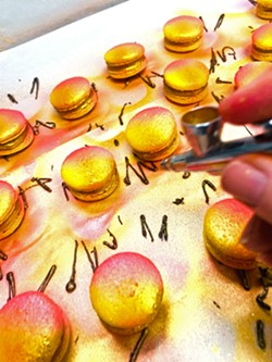 ARTIST AT WORK Monika Anderson's salted caramel macarons are airbrushed yellow, orange, and hot pink; dusted with 24-carat edible gold powder mixed with vodka; then topped off with pure dark chocolate and a pinch of salt crystals. - PHOTO COURTESY OF MONIKA'S MACARONS