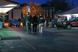BAD BOYS, BAD BOYS :  Sheriff's deputies and probation officers took an unidentified man into custody at a Paso Robles motel as part of a sweeping anti-narcotics operation headed by the FBI. Faces have been blurred at the request of law enforcement for the safety of the narcotics officers. - PHOTO BY STEVE E. MILLER