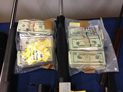 LAWYERS, GUNS, AND MONEY :  An early morning raid on eight residences in the Nipomo area netted more than 60 weapons, about $155,000 in cash, and 12 arrests for alleged drug trafficking activity. - PHOTO COURTESY OF SLO COUNTY SHERIFF'S OFFICE