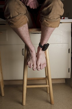 STRAPPED :  Rather than serve a sentence in jail and risk losing his house and job, Jim opted for house arrest where he's tethered by an electronic ankle bracelet. - PHOTO BY STEVE E. MILLER
