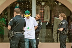 """TOO MUCH FUN:  A reveler is taken into custody by the San Luis Obispo Police Department on the morning of St. Patrick's Day after allegedly throwing a water bottle. It was also his 21st birthday. Well-known party holidays like St. Patrick's Day, Halloween, and Mardi Gras see a heavy police presence in San Luis Obispo, which becomes a """"double fine zone"""" during those times. - FILE PHOTO BY KAORI FUNAHASHI"""