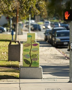 ORNAMENTAL, AS WELL AS USEFUL:  Aaron Landrith, a senior architecture student, discusses the city's role in curating artistic taste through its commissioning of painted utility boxes, such as this one by local artist Marcia Harvey. - PHOTO BY STEVE E. MILLER