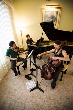 THREE'S HARMONY:  Scott Yoo (left), John Novacek (middle), and Madeleine Kabat (right) rehearse one of Russian composer Georgy Sviridov's piano trios at the home of festival sponsor Samantha Curran. - PHOTO BY HENRY BRUINGTON