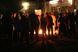 GATHER 'ROUND THE FIRE :  Campers warm up before the start of a Hot Licks Dance concert. - PHOTO BY GLEN STARKEY