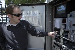 WHERE THE MAGIC HAPPENS :  City traffic engineers, like Jake Hudson, used to have to drive out to an intersection utility box to fix traffic signals or the video system. Now, everything happens remotely. - PHOTOS BY STEVE E. MILLER