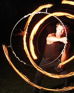 RING OF FIRE :  Grant Leonard spins circles during an informal Fluid Luminescence gathering. - PHOTO BY STEVE E. MILLER