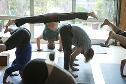 WHERE THE SUN DOES SHINE:  Peter Sterios (pictured, in headstand) leads an early-morning yoga class at his studio, m.Body Yoga & Massage. - PHOTO BY STEVE E. MILLER
