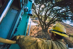 BLAZE OF GLORY:  Firefighters work around the clock to battle the Cuesta Fire. The blaze started Aug. 16 by a car and grew to more than 2,500 acres by Aug. 19. Cal Fire officials hope to have the blaze contained by Aug. 26. - PHOTO BY KAORI FUNAHASHI