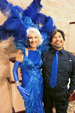 "LAND OF DIXIE:  Dixie Parker wears fully feathered and fabulous Central Coast Follie outfit with Jason Sumabat, director of the 13th annual Benefit for Parkinson's Research ""California Dreamin"" show. - PHOTO BY REBECCA LUCAS"