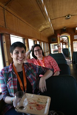 CHUG INTO CHOWTIME:  Santa Margarita Ranch is known for its award-winning vineyards and ancient barn as well as the old timey train that chugs through the property during Sunset Savor the Central Coast each year. Pictured, New Times Arts Editor Jessica Peña and intern Adriana Catanzarite take a break from the food to travel back in time. - PHOTO BY HAYLEY THOMAS