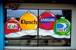 BRANDED BULBS:  Though it is a creative discipline, window painting is primarily used for advertisement. Here, Loney incorporates brand names into a seasonal scene. - PHOTO COURTESY OF MIKE LONEY
