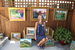 OPEN AIR:  Christine Cortese sits with her oil paintings in the driveway of fellow artist for Art Obispo's Open Studios Art Tour 2015. - PHOTO BY REBECCA LUCAS