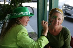 GET YOUR SPIRIT ON:  Longtime face painter Teresa Schmidt (481-5093) set up shop in front of McCarthy's Irish Pub, here painting Laurel White. - PHOTO BY GLEN STARKEY