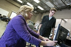 TEACHER AND TECH :  Liz Moore, a teacher in the photography and videography class, helped Jimi Lester with a display problem. - PHOTO BY STEVE E. MILLER