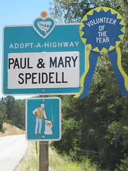 SIGN OF THEIR TIME:  Paul and Mary Speidell were honored in 2011 by Caltrans with this ribbon placed on their road sign, recognizing their 25 years of picking up litter - on Highway 46 West. - PHOTO COURTESY OF CALTRANS