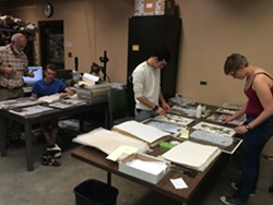 PRESERVE:  Volunteers dry and glue plant samples to archival paper. - PHOTO BY JENN YOST