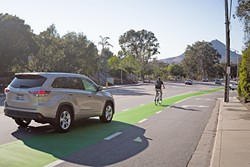 """GREEN LANES:  SLO hopes to introduce more """"protected bike lanes,"""" such as this stretch on California Boulevard, to separate bikers from high-speed traffic. - PHOTO BY KAORI FUNAHASHI"""