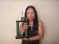 TROPHY MOM :  Maria Hernandez holds a trophy she won as the first student in Atascadero High School history to earn all her credits in two years. - PHOTO COURTESY OF ECONOMIC OPPORTUNITY COMMISSION