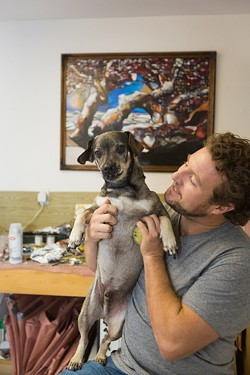 MAN'S BEST FRIEND:  Jordan Quintero hangs out with his dog, Beckman, at his studio in Arroyo Grande. Note: Quintero is the one on the right. - PHOTO BY KAORI FUNAHASHI