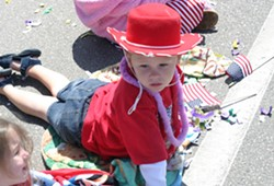 WONDER YEARS :  A cowboy-hatted tyke gazes in amazement as the parade rolls past. - PHOTO BY GLEN STARKEY