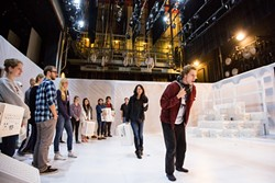 FOLLOW THE LEADER:  In 'The Other Shore,' the audiences becomes a part of the play. Before the play begins, they're led to the stage and can pick portable seating (white crates) that move throughout the show. - PHOTO BY KAORI FUNAHASHI