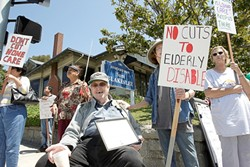 NOT WITHOUT A FIGHT :  If state budget cuts go through, 71-year-old Dale Grube (center, seated) worries he'll lose the freedom of his apartment, because without his caretaker he'll be forced to live in a convalescent home. - PHOTO BY STEVE E. MILLER