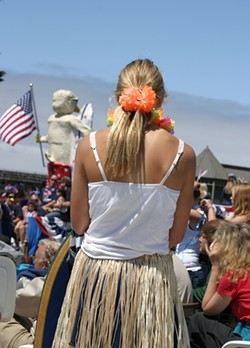 CALIFORNIA GIRL :  A hula girl watches the rest of the parade after her group finishes their hula duties. - PHOTO BY GLEN STARKEY