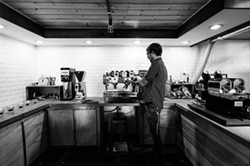 COFFEE CRAFTSMAN:  Part chemist, part coffee guru, Kreuzberg roaster Shawn Clark meticulously roasts batches of specialty beans in the coffee shop's onsite roastery. - PHOTO BY KAORI FUNAHASHI