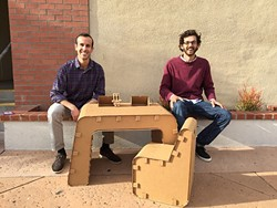 JUST ONE OF THE GUYS:  Jake Disraeli (left) and Justin Farr (right), owners of The Cardboard Guys, sit with their company's cardboard desk and chair with their logo and mascot, Cardboard Corey. - PHOTO BY REBECCA LUCAS