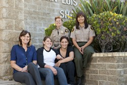 """CREDIT DUE :  Friends Kaya and Barbara (seated center) are two of the first """"generation"""" of AB109 inmates released from SLO County Jail to have found success and sobriety after release. They told New Times that success has everything to do with new programs run by—and the relationships built with—local jail officials such as new Jail Programs Manager Alison Ordille (seated left), correctional Deputy Lacie Silviera (back center), and Correctional Cpt. Michele Cole. - PHOTO BY STEVE E. MILLER"""